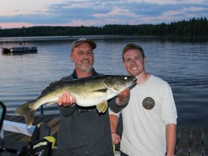 2 men holding a large walleye at dusk at Cedar Point resort in Marcell, MN