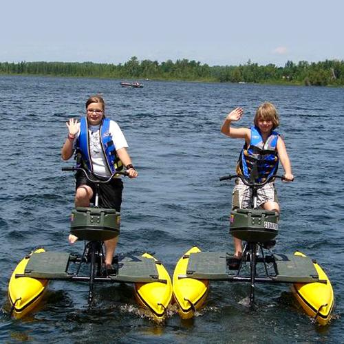 2 Kids using the cedar point resort water bikes amenity on the lake