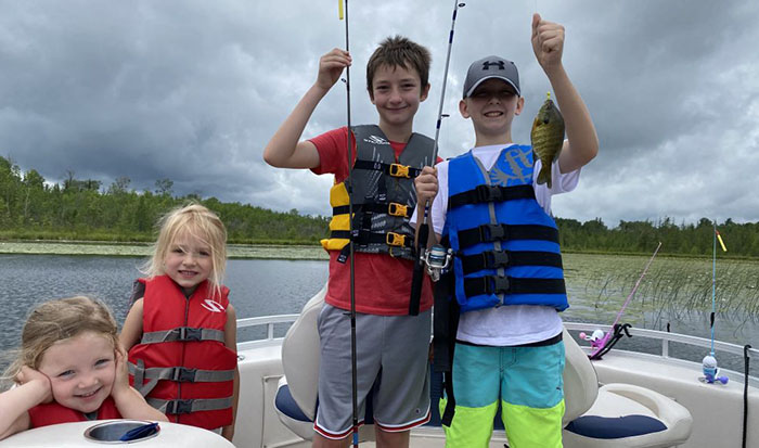 Two young girls and two boys fishing on a boat at Cedar Point resort